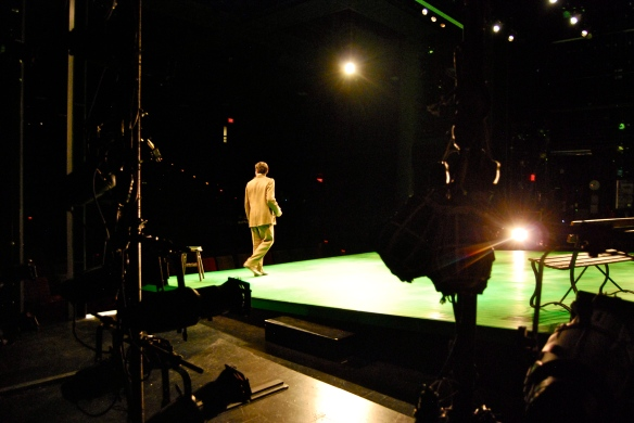 From the wings - where the actors wait to go on stage - we view Georges alone.
