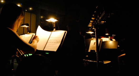 The pit orchestra for the production sits behind the stage.